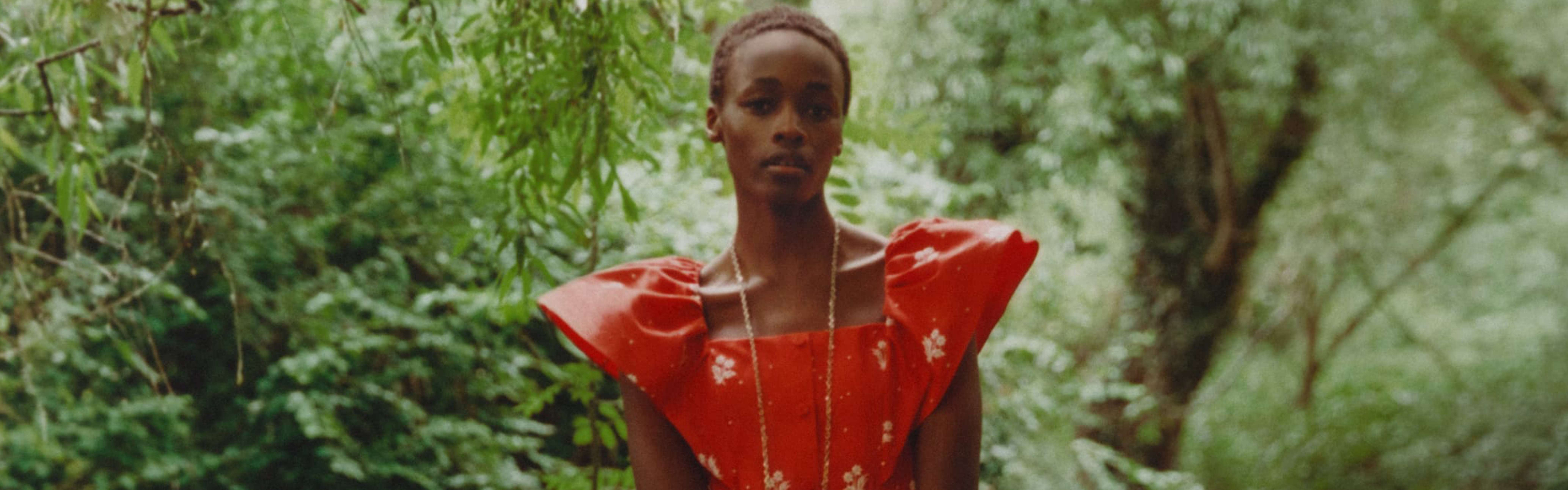 Model in statement red, bold shoulder, ERDEM luxury dress, accessorised with a long necklace.